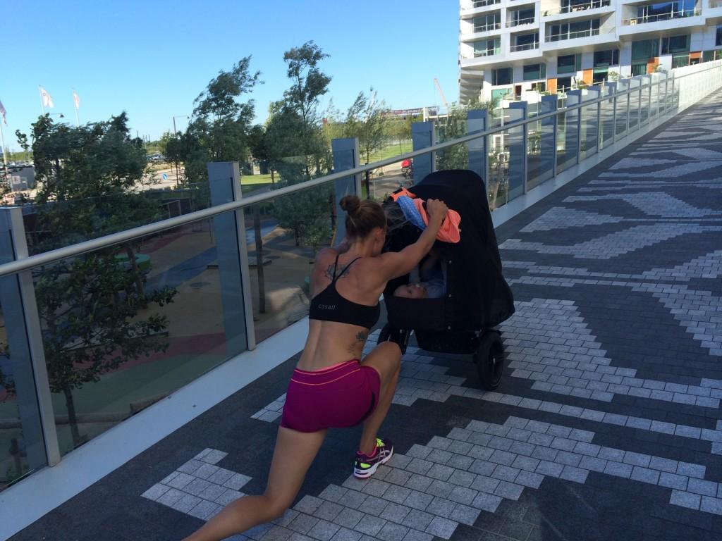 kvinde skubber barnevogn op ad bakke