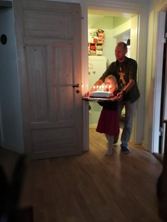 Far hjælper den stolte fødselar med at bære kagen ind