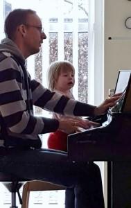 Agnes med sin morfar, han lærer hende at spille klaver